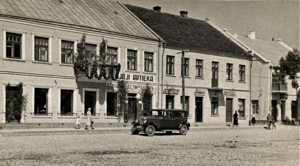 """Viešosios aikštės vakarinė kraštinė. Kairėje – provizoriaus Stasio Ščefanavičiaus vaistinė """"Naujoji aptieka"""". Už jos – kirpyklos, Kretingos žemės ūkio smulkaus kredito banko bei manufaktūros ir gatavų rūbų parduotuvės pastatas. Apie 1936–1939 m. Kretingos muziejus."""