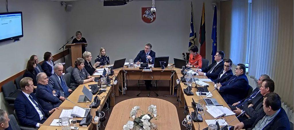 """Svarstant Švietimo tinklo pertvarką Tarybos posėdžių salėje kairėje sėdintys socialdemokratai ir valstiečiai laikėsi kitokios nuomonės  nei priešais esanti valdančioji dauguma. Stop kadras iš """"Youtube""""  tarybos posėdžio vaizdo įrašo."""