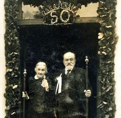 Marija ir Aleksandras Tiškevičiai, 1937 m. liepos 27 d. stovintys  Kretingos dvaro rūmų paradinio įėjimo tarpduryje su auksinių vestuvių lazdomis rankose.