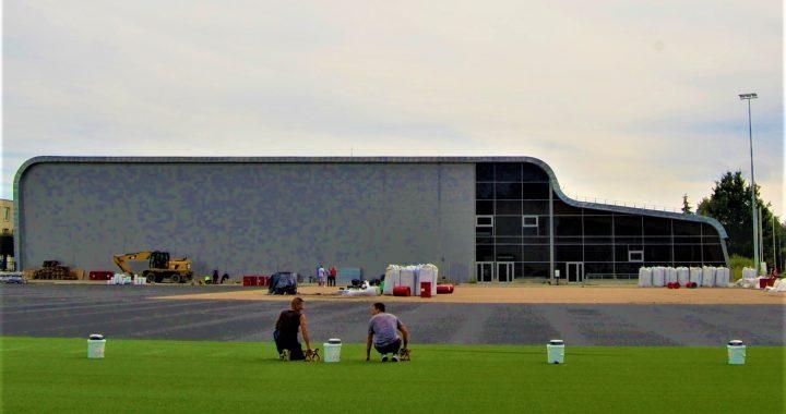 Kretingiškių taip laukiamas naujasis futbolo stadionas jau dengiamas dirbtine žalia danga. Ligitos Sinušienės nuotr.