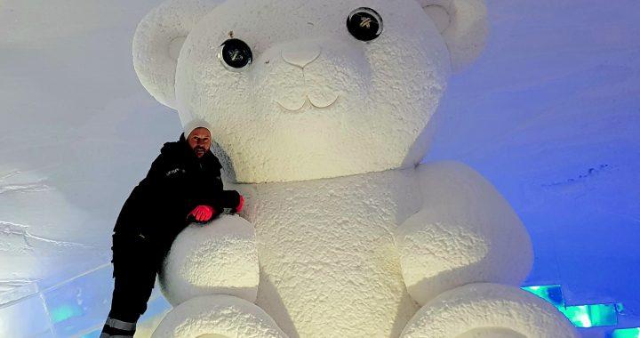 Andrius Petkus pozuoja pasilipęs ant savo skulptūros – 3 m pločio ir 5 m aukščio sniego meškino. Asmeninio archyvo nuotr.
