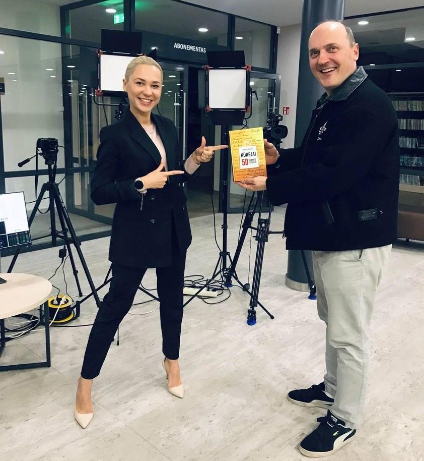 """Brigita Barkauskaitė su džiaugsmu iš svečio Giedriaus Drukteinio priima dovaną bibliotekai - jo knygą """"50 sėkmės istorijų""""."""