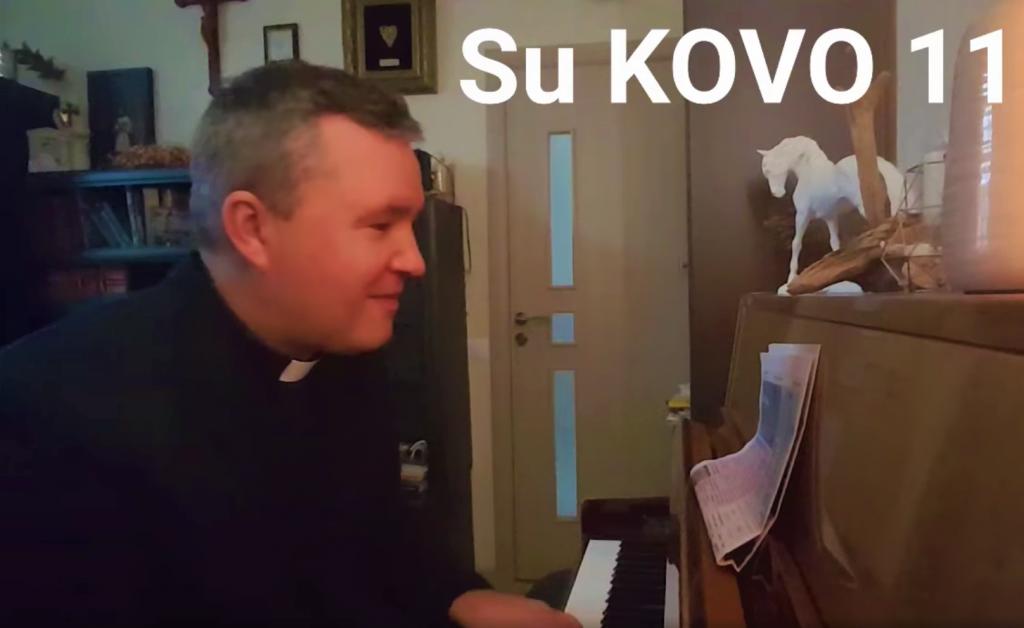 """Vydmantų klebonas Karolis Petravičius skambina naują kūrinį, o žodžius skaito tiesiai iš """"Švyturio"""" laikraščio."""