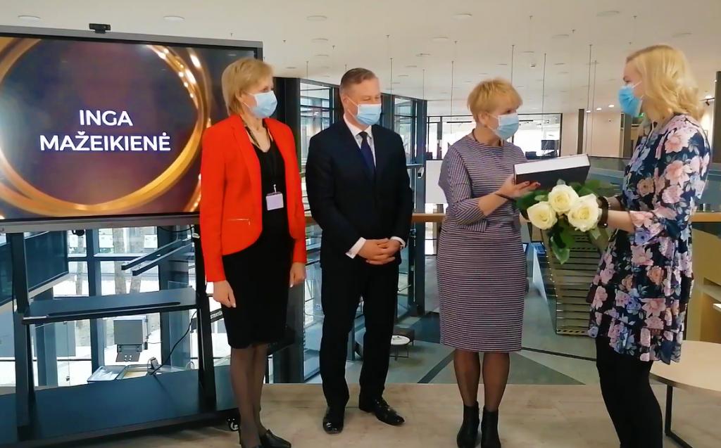 Įteikiamas apdovanojimas Kretingos rajono M.Valančiaus bibliotekos Baublių filialo vyresniajai bibliotekininkei Ingai Mažeikienei. Stop kadras iš Youtube įrašo.