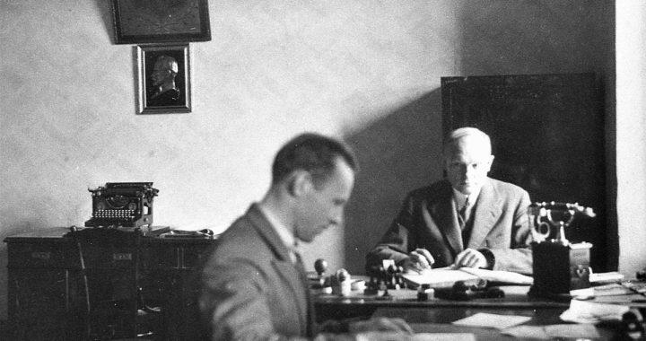 Lietuvos ūkio banko Kretingos skyriaus vedėjas Simonas Jurgis Simutis (antrame plane) už darbo stalo. Simono J. Simučio nuotr. 1931 m. Iš Kretingos muziejaus ikonografijos rinkinio.