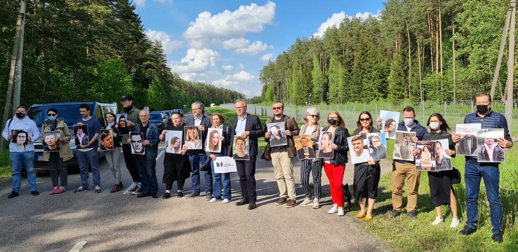 """Vaiva Radikaitė-Žukienė (šešta iš dešinės) su koelgomis iš Lietuvos ir """"Reporteriais be sienų"""" Medininkų posežte stovėjo, rankose lailydami Baltarusijoje kalinamų žurnalistų nuotraukas. Dainiaus Radzevičiaus nuotr."""